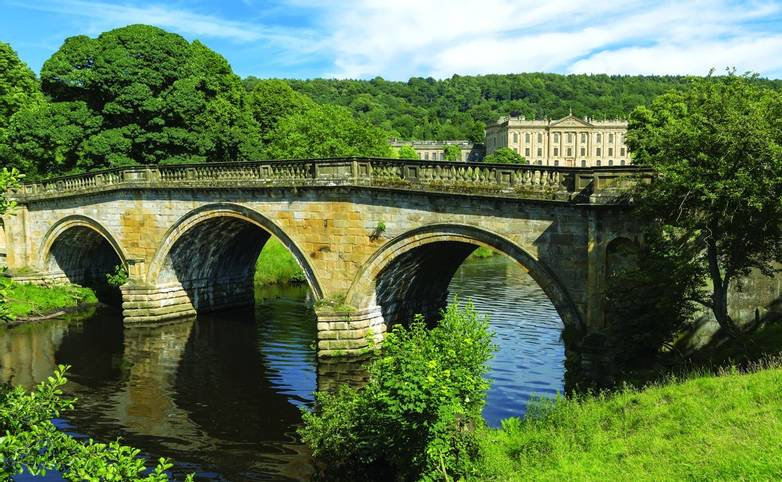 Stone road bridge over the River Derwent at Chatsworth house estate, Derbyshire.