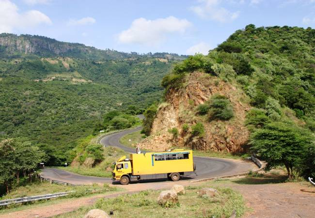 African overland truck driving down mountain