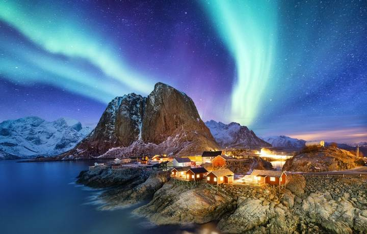 Aurora Borealis above Reine, Lofoten islands, Norway. Nothen light, mountains and houses. Winter landscape at the night time…