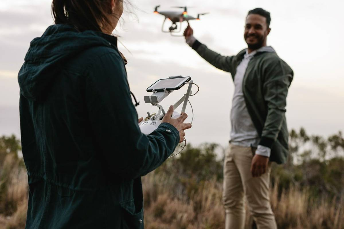 Woman with remote control and  man holding a flying drone in countryside. Young couple flying drone in countryside.