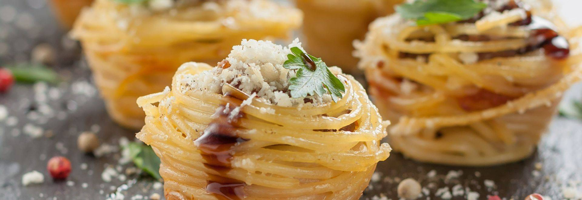 muffins from spaghetti with cheese and meatballs on a white background