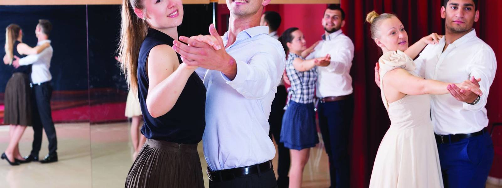 Young positive people dancing together slow ballroom dances in pairs