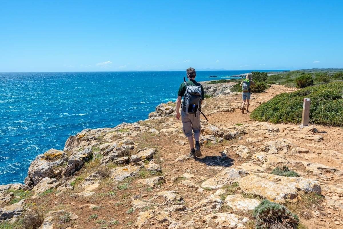 Hikers on a coastal path by the sea in Menorca, Balearic islands, Spain