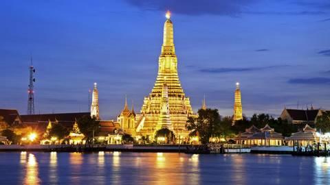 Twilight time of Wat Arun across Chao Phraya River during sunset in Bangkok, Thailand
