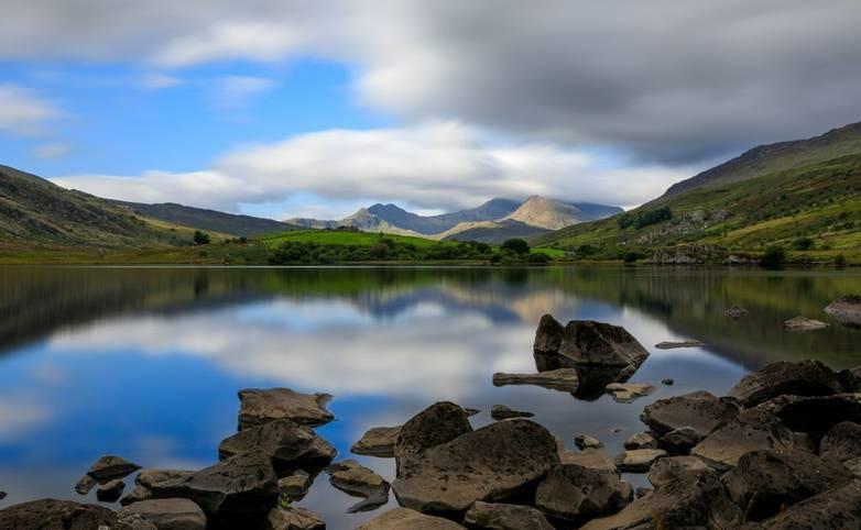 The summit of Snowdon with a cloud washing over it. The lake, Llynnau Mymbyr, Reflecting the scene. Snowdonia (Eryri), Wales…