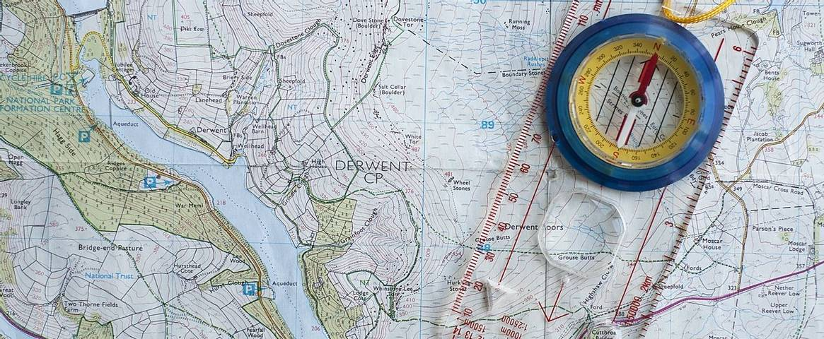 A map of the Derwent Reservoir in the Peak District, UK, with a compass laying on top of it