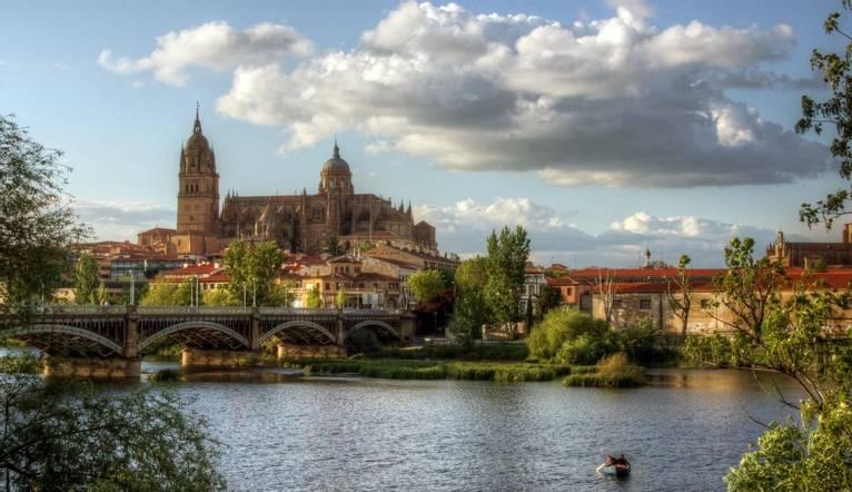 Salamanca old town, Roman Bridge and small boat.