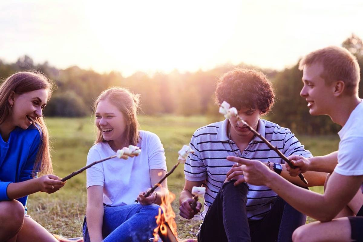 Photo of friendly company of friends have picnic outdoor, roast marshmallows over campfire, have positive expressions, pleas…