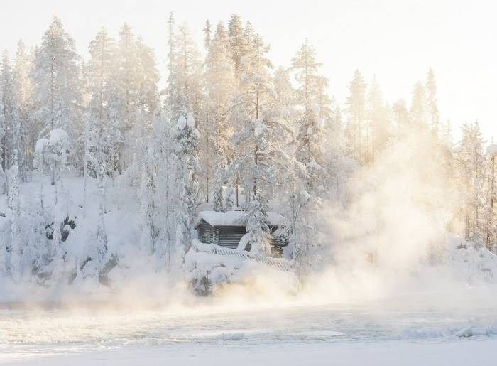Small log cabin behind vaporing river in winter in Lapland, Finland