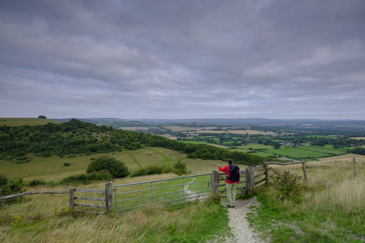 Cloudy overcast summer sunrise over the South Downs Way footpath from A middle aged male walker with backpack admiring the v…