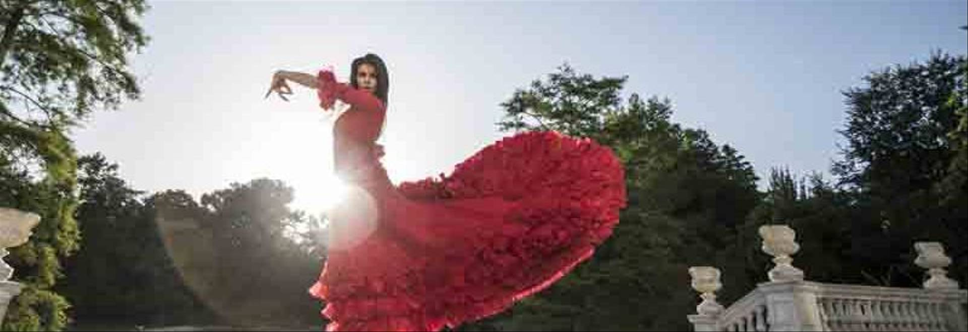 Woman dressed in red dancing flamenco on terrace at backlight