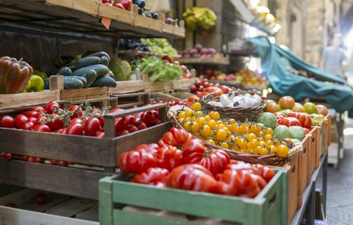Fresh and healthy vegetables and colorful fruit in front of a shop in a picturesque street in Italy