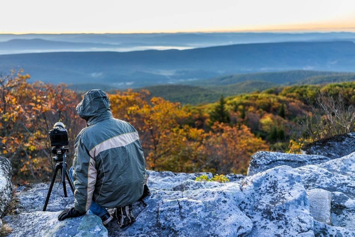 Sitting young man photographer with camera, gear, and tripod on cold autumn morning in jacket in Bear Rocks, West Virginia t…