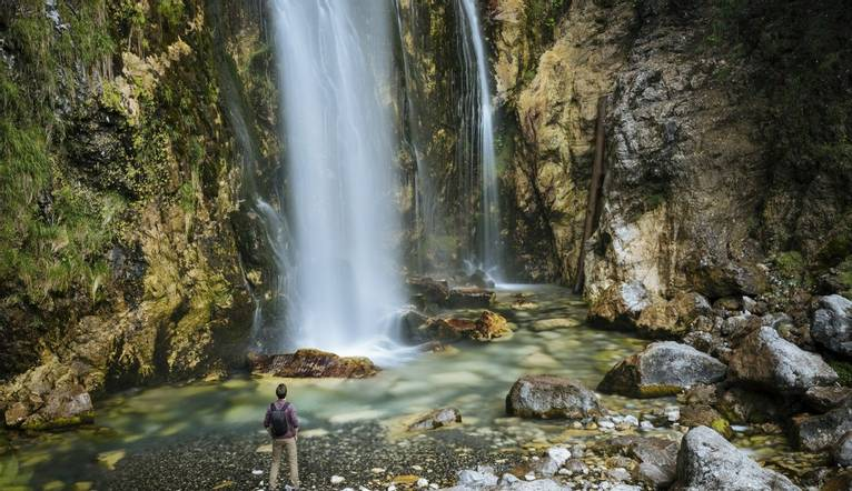 Man looking up at Theth Waterfall, Theth, The Accursed Mountains, Albania