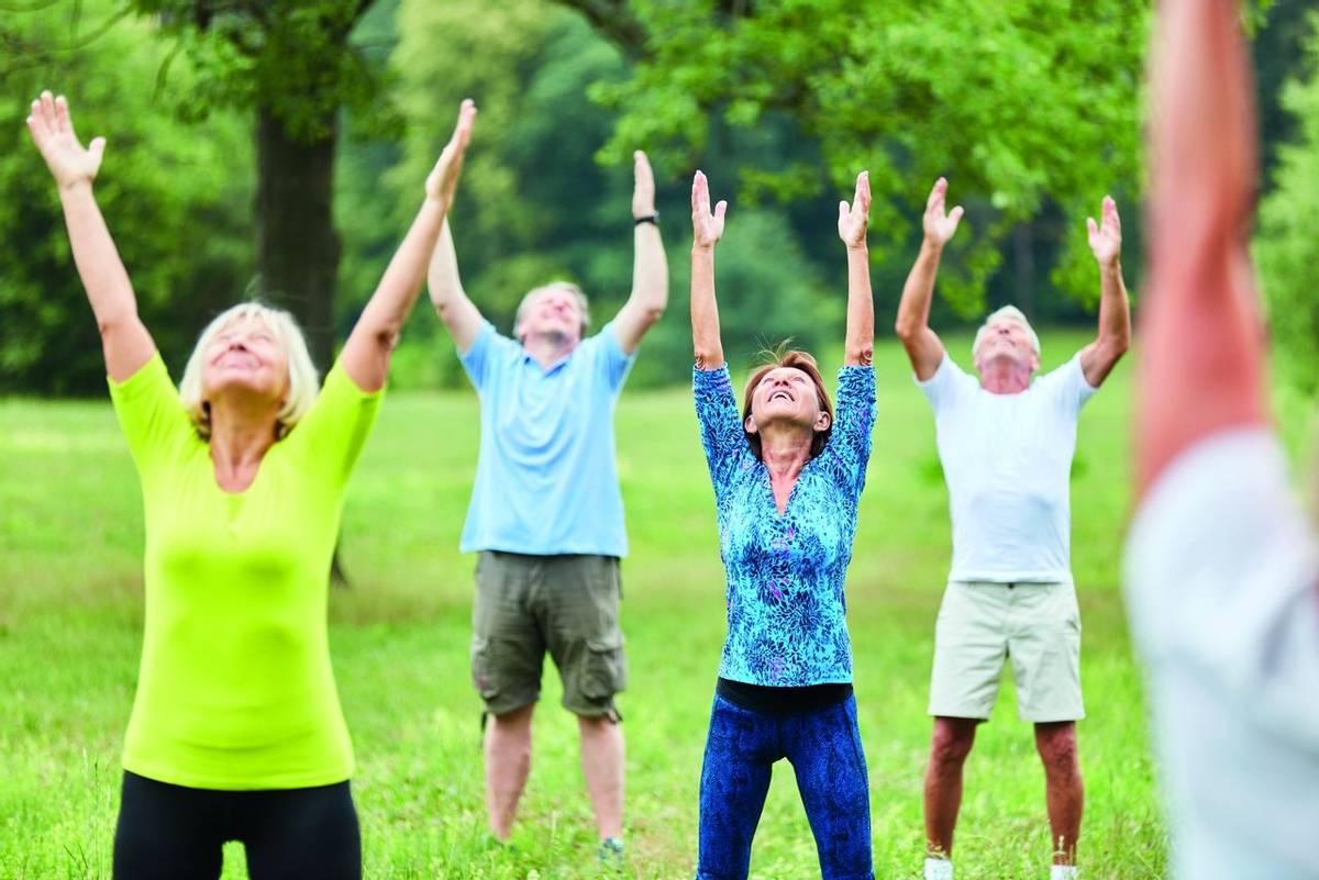 Aktive Senioren beim gesunden Stretching in einem Reha Fitness Kurs im Sommer