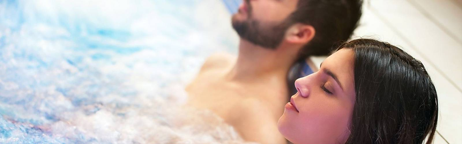 Close up portrait of young couple relaxing in spa jacuzzi. Couple together in bubble water with eyes closed.