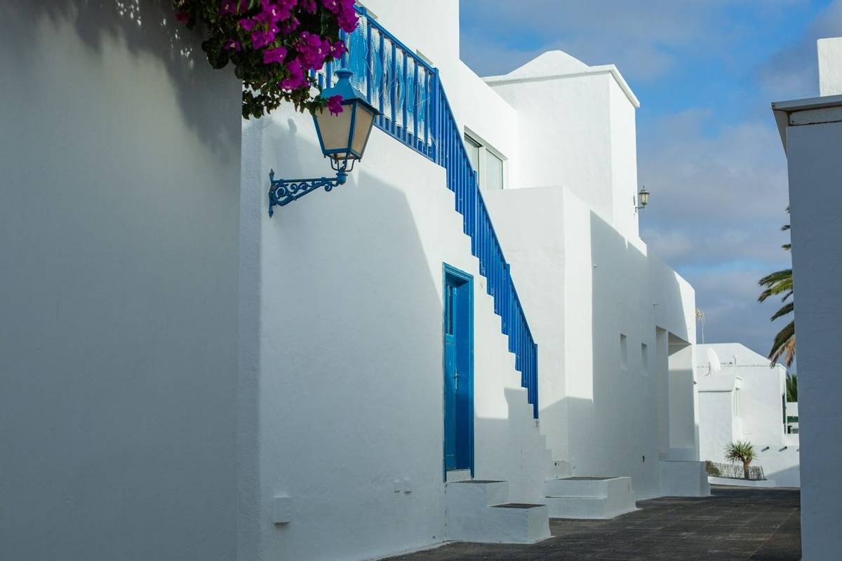 Beautiful white two-story houses for holidaymakers in Costa Teguise on Lanzarote island. Route to the ocean.