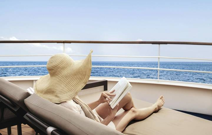 Lady reading a book on a sun bed on the deck, Silver Muse