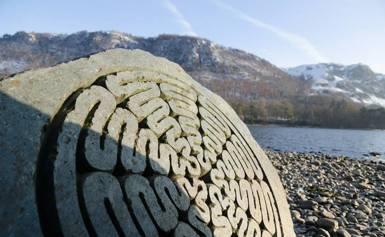 The Lake District, Keswick, England, 01/17/2016, Winter lakeside view with carved stone memorial in the foreground