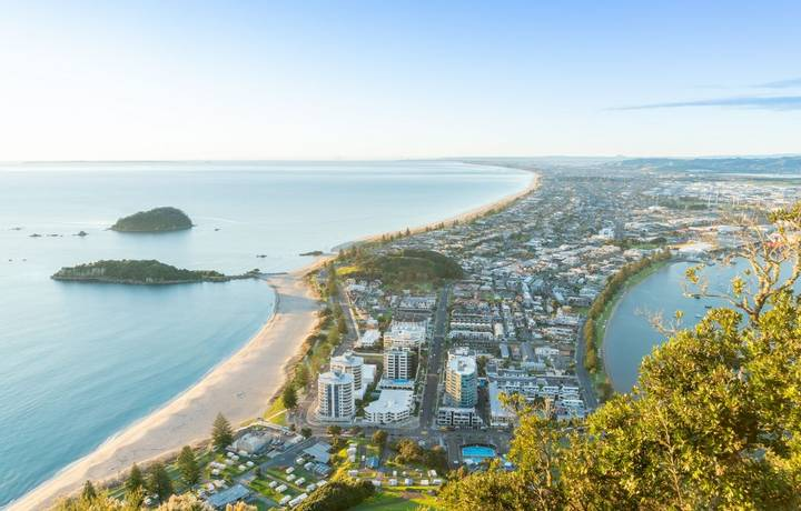 Mount Maunganui stretches south out below as sun rises on horizon and falls across ocean beach and buildings below