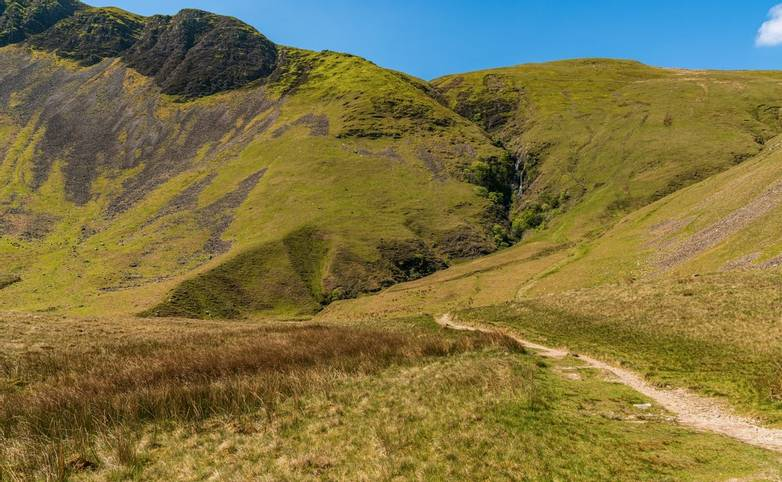 A footpath in the Howgill Fells with Cautley Spout in the background, near Low Haygarth, Cumbria, England, UK