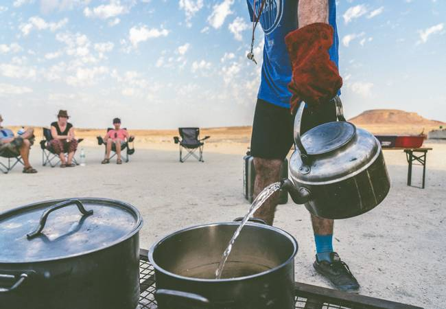 Central Asia overland group camping in the desert and preparing dinner