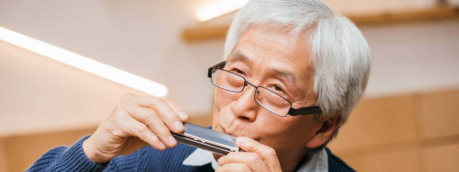 portrait of happy senior asian man playing harmonica