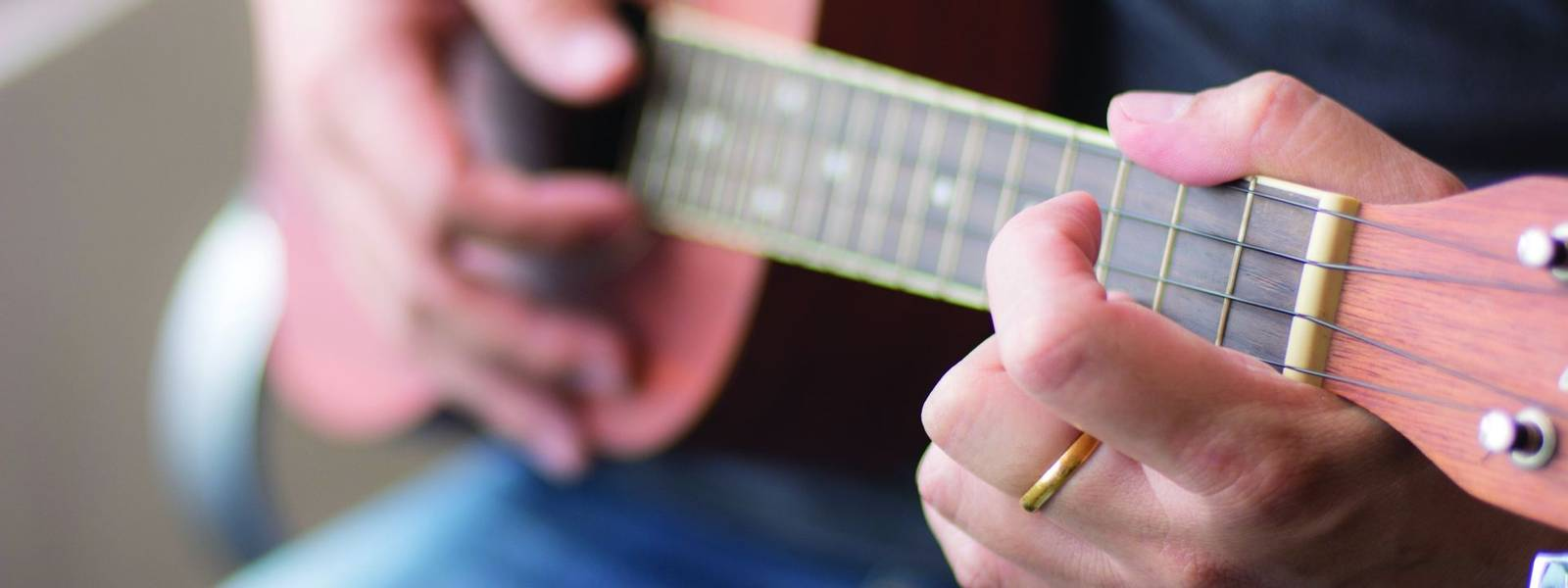 Man playing Ukelele with selective focus