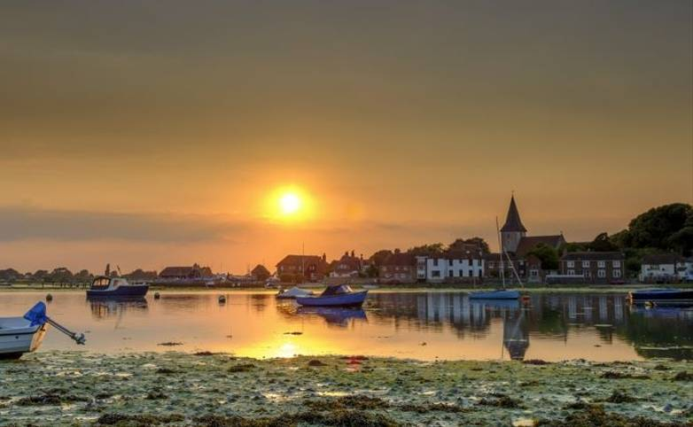 Summer sunset over Bosham Harbour and village with the church spire of Holy Trinity Church, West Sussex, UK
