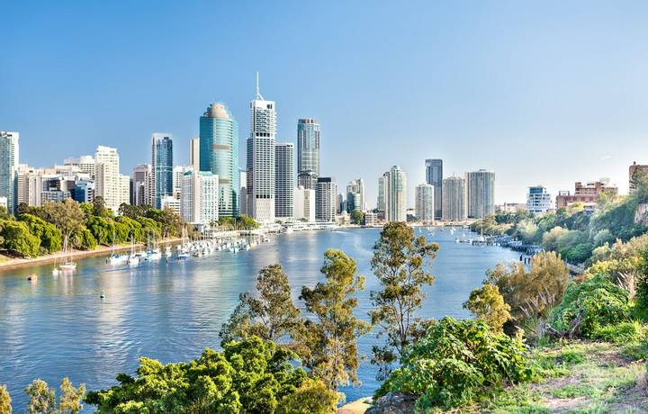 Blue water river surrounded by trees beside a modern cityscape including lots of tall buildings  under blue sky called Brisb…
