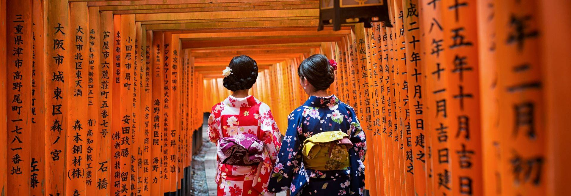 Two geishas wearing traditional japanese kimono among red wooden Tori Gate at Fushimi Inari Shrine in Kyoto, Japan. Fushimi …