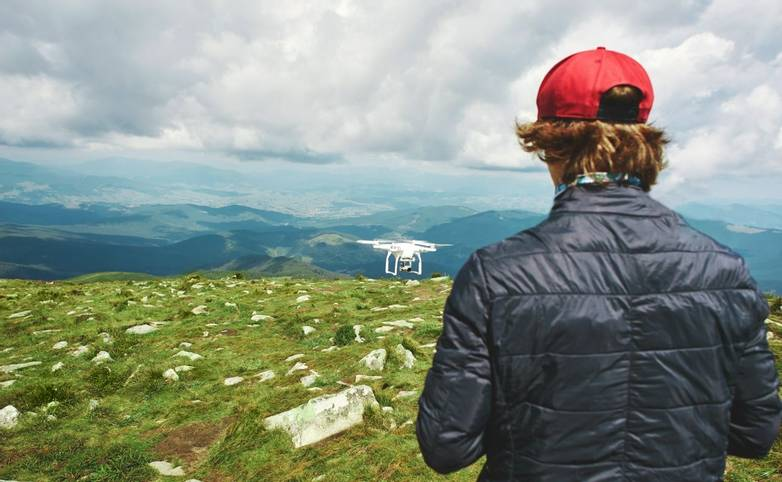 man playing with the drone. drone quadcopter with digital camera in the mountains. The drone with camera takes pictures of t…