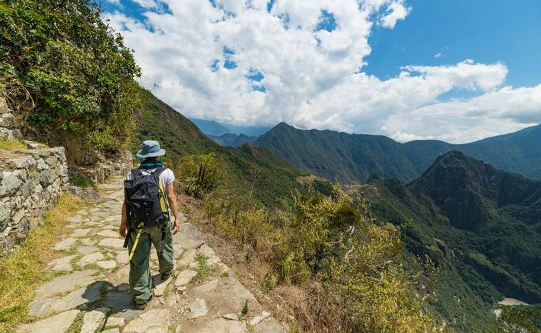 Backpacker exploring the steep Inca's footpaths of Machu Picchu, the most visited travel destination in Peru. Summer adventu…