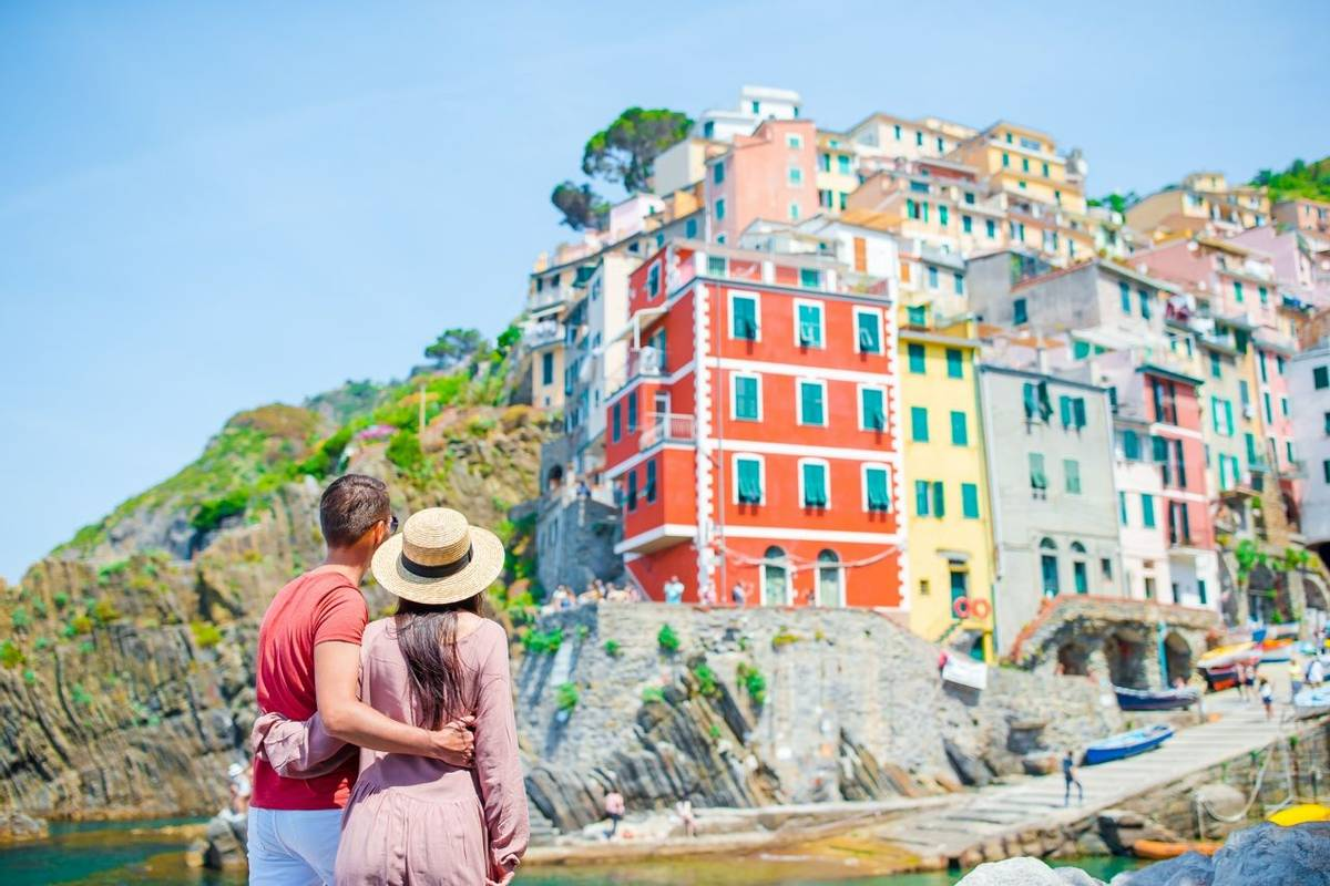 Young family with great view at old village Riomaggiore, Cinque Terre, Liguria, Italy. European italian vacation.