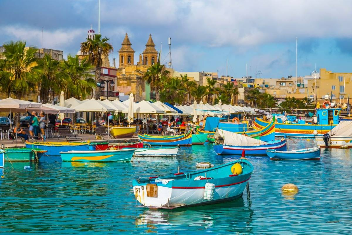 Marsaxlokk, Malta - Traditional colorful maltese Luzzu fisherboat at the old village of Marsaxlokk with turquoise sea water …
