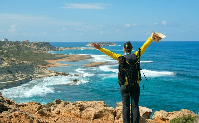 Happy hiker woman with backpack standing on the sea shore pulls hands to the sky and enjoying life. Sunny day on Cyprus.