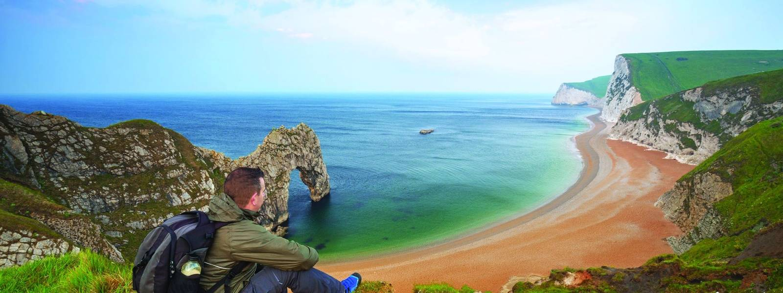 Man watching sunrise over Jurassic coast of Dorset, UK