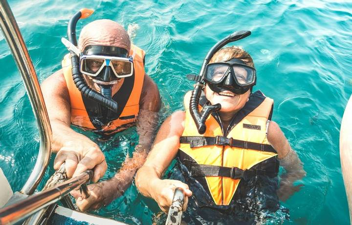 Retired couple taking happy selfie in tropical sea excursion with life vests and snorkel masks - Boat trip snorkeling in exo…
