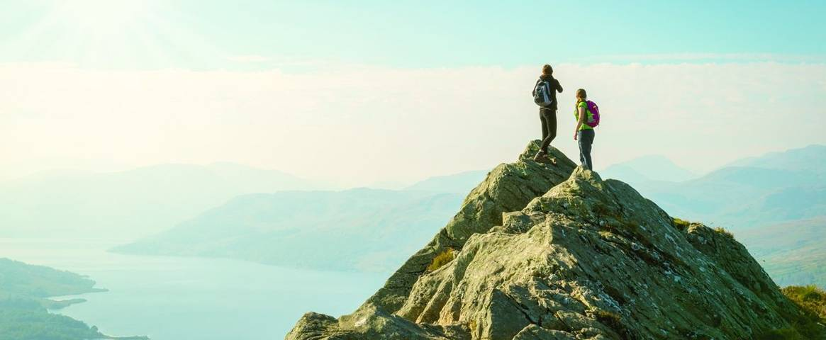 Hikers enjoying the view from the top of the mountain in the Highlands of Scotland