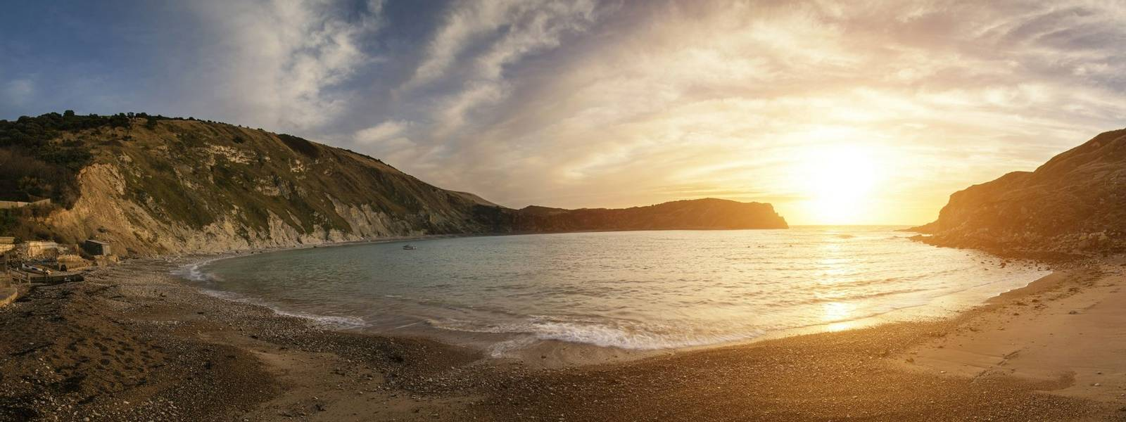 Beautiful sunrise panorama landscape over Lulworth Cove in Dorset