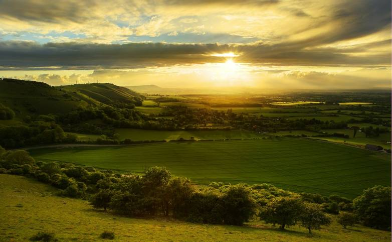 Stunning countryside landscape with sun lighting side of hills at sunset