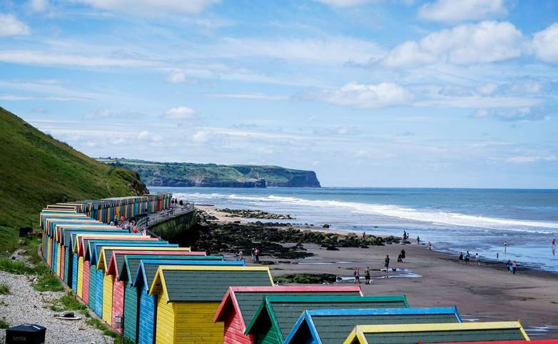 Whitby, North Yorkshire, England - July 1, 2017:,UK - Row of colorful beach huts at Whitby beach on a beautiful sunny day in…