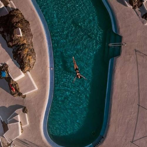 Woman swimming in a pool, relaxed on holiday