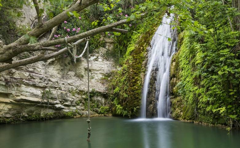 Waterfall falling into a  lake. Bath of Aphrodite. Cyprus. Tourist destination, tourist attraction, famous mythological site