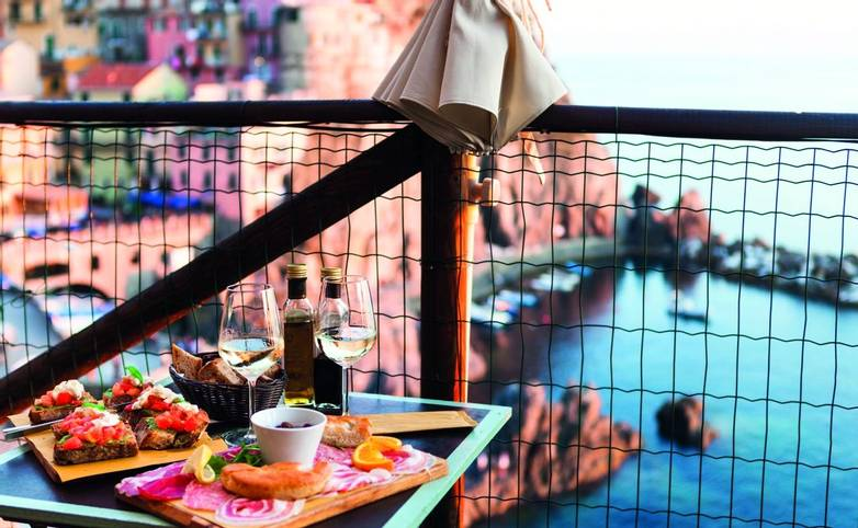 Romantic dinner for two at sunset. White wine and Tasty italian snack: fresh bruschettes  and meat on the board in outdoor c…