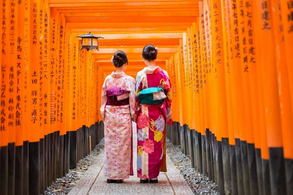 Geishas among red wooden Tori Gate at Fushimi Inari Shrine in Kyoto, Japan