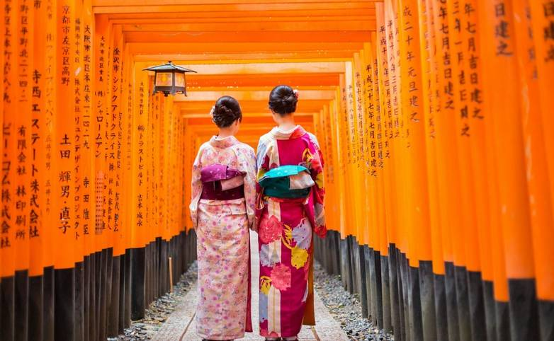 Geishas among red wooden Tori Gate at Fushimi Inari Shrine in Kyoto, Japan
