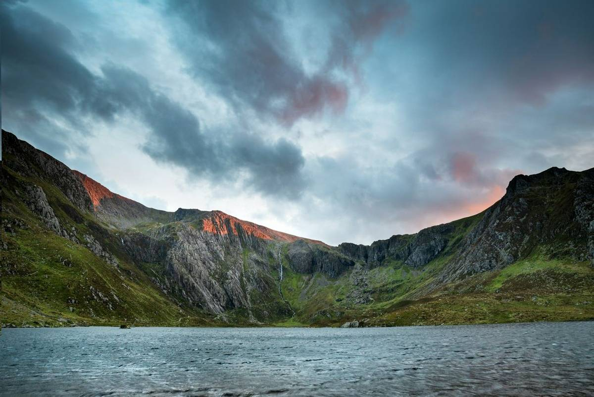 Beautiful sunset landscape image of Llyn Idwal and Devil's Kitchen in Snowdoina during Autumn evening