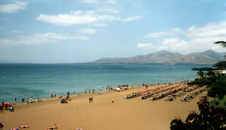 Tourists relaxing on the long beach at Puerto del Carmen, the main tourist spot on the island of Lanzarote, Canary Islands, …