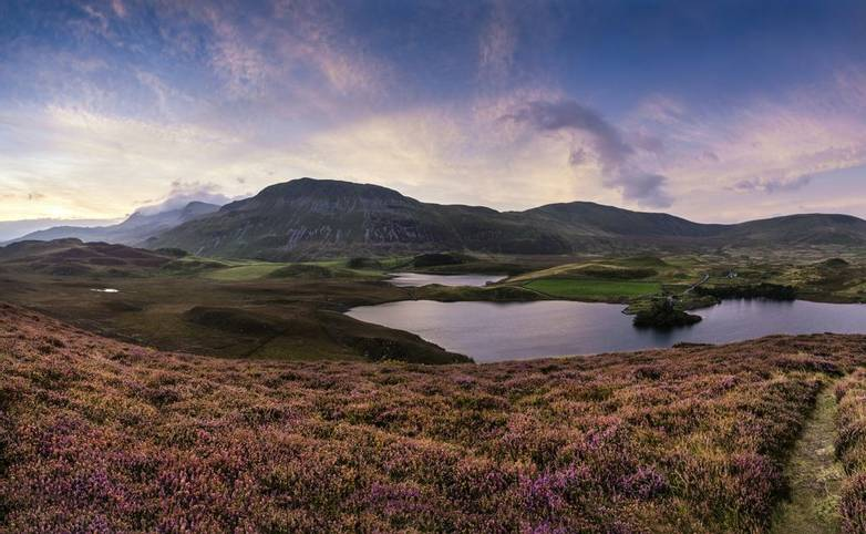 Beautiful vibrant sunrise landscape over Cregennen Lakes with Cadair Idris in background in Snowdonia